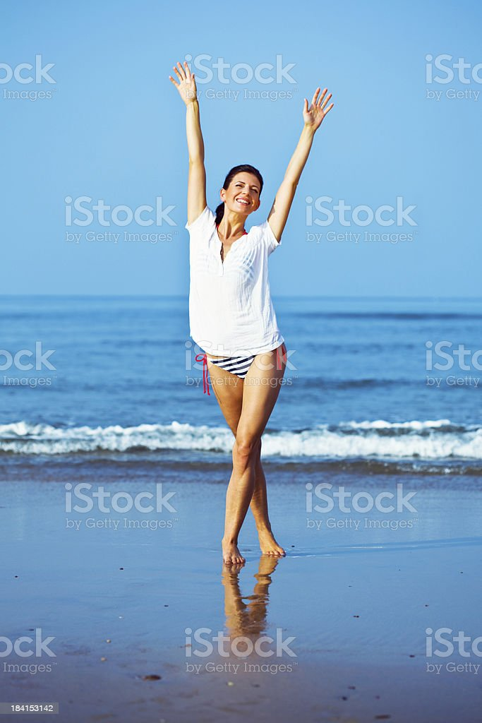 Happy summer holiday Pretty woman standing on the tropical beach and raising her arms. Looking at camera and smiling. 25-29 Years Stock Photo