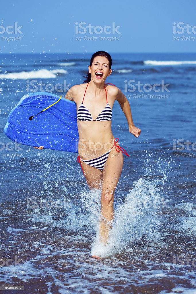Happy summer vacation Happy woman wearing striped bikini holding bodyboard and running in ocean. Active Lifestyle Stock Photo