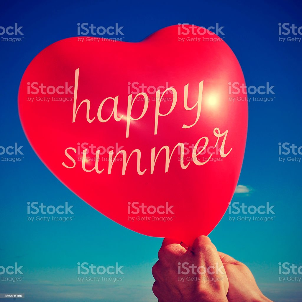 happy summer written in a heart-shaped balloon stock photo