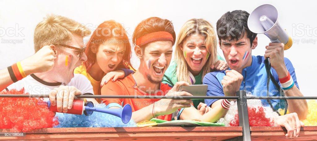 Glückliche Fans aus verschiedenen Ländern gerade Fußball auf Smartphone mit Online-Sport-Abonnement - Schwerpunkt Zentrum Mensch - verrückter Fan feiert ein Ziel in Welt-Fußball-Spiel - Spaß-Konzept – Foto