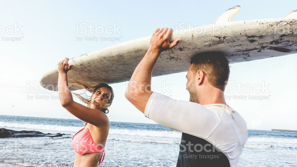 Happy surfer couple bringing having fun on the beach - Tourists people doing surf in summer vacation - Travel, extreme sport and healthy lifestyle concept - Focus on man hand board stock photo