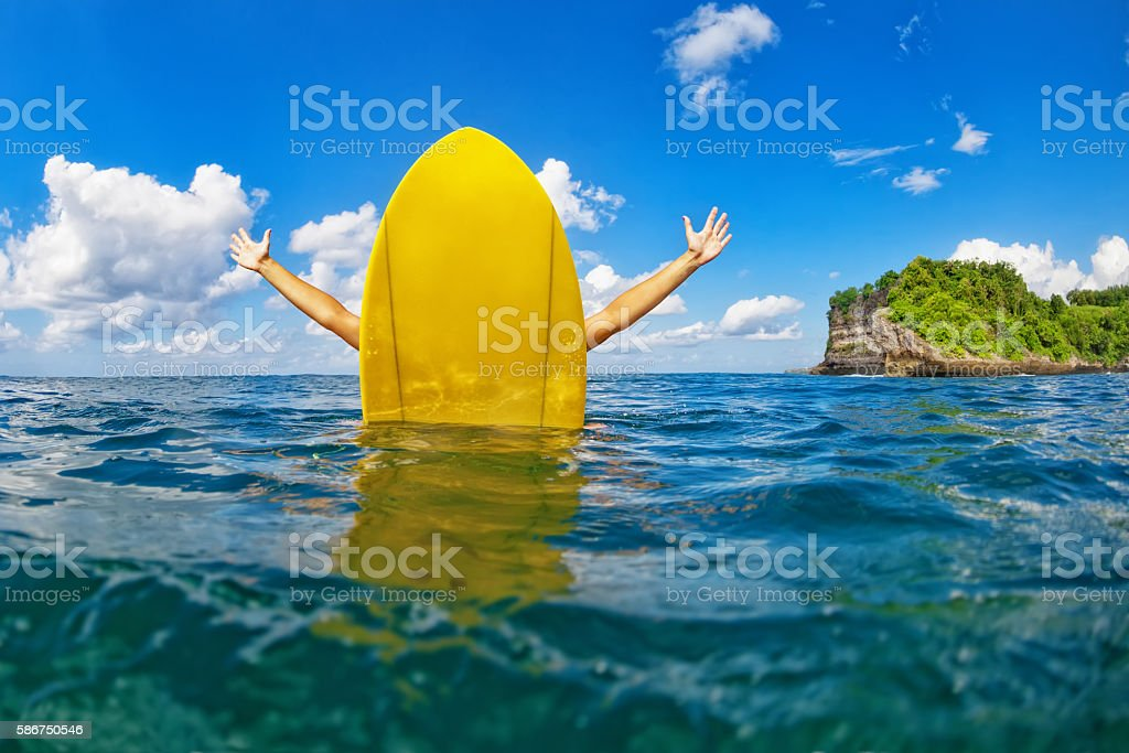 Happy surfer girl sit on yellow surfboard in ocean stock photo