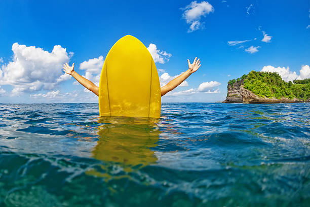 Happy surfer girl sit on yellow surfboard in ocean stock photo