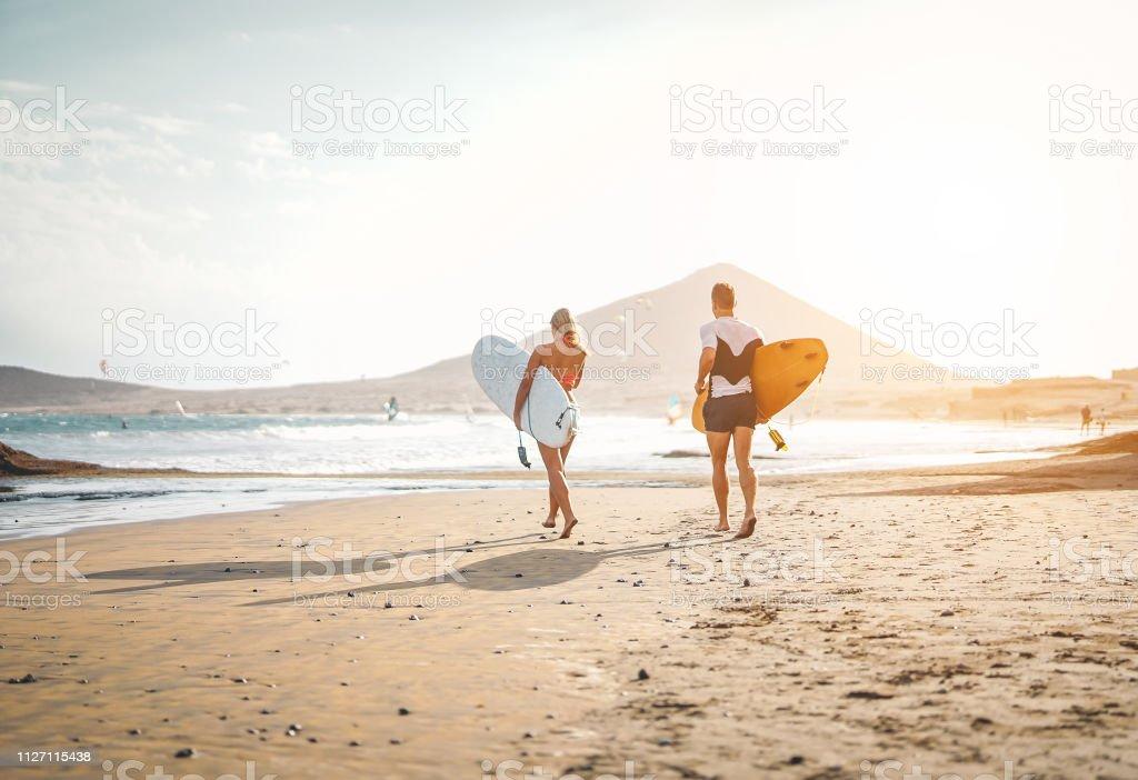 Glückliche Surfer mit Surfbrettern auf dem Strand - sportliches Paar Spaß Surfen zusammen bei Sonnenuntergang - Extreme Beziehung, Menschen, Sport und Jugend Lifestyle-Konzept - Lizenzfrei Aktiver Lebensstil Stock-Foto