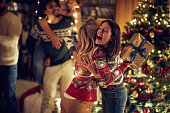istock Happy surprise for friend with present at Christmas. 1187136793
