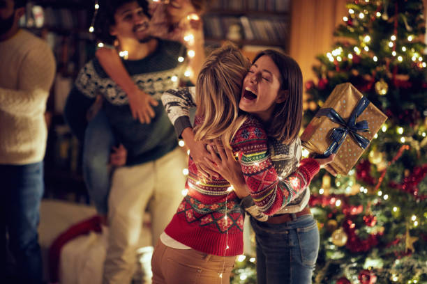Happy surprise for friend with present at Christmas. stock photo