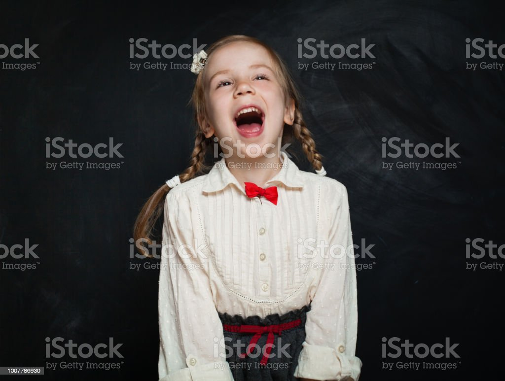 Happy surprised child having fun and laughing on chalk board...