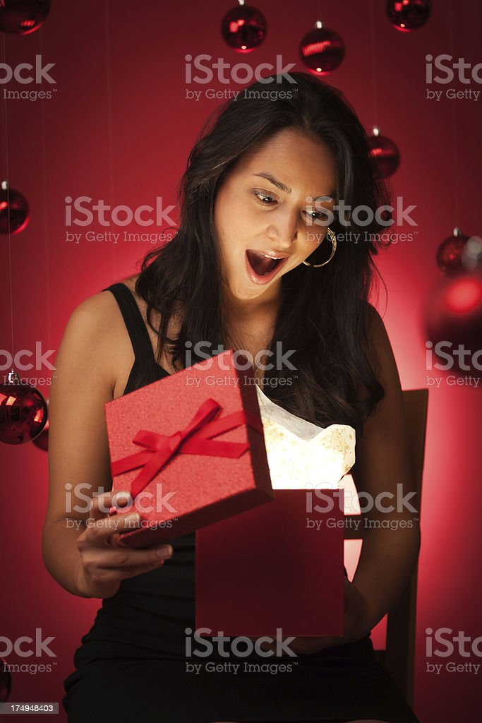 Happy Surprised Hispanic Model Opening Magical Christmas Gift royalty-free stock photo