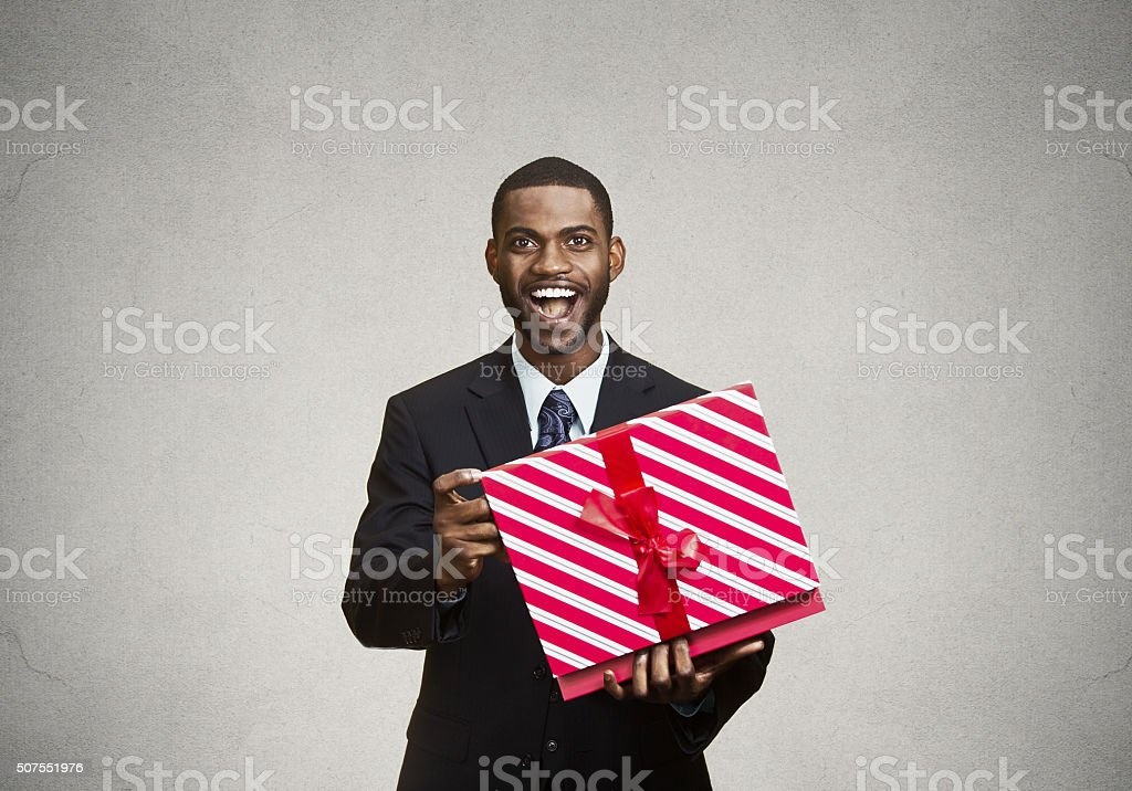 Happy, surprised man receiving gift from someone stock photo