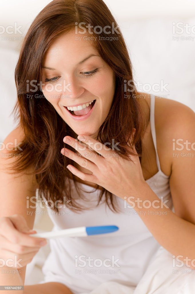 A happy surprised woman looking at a pregnancy test stock photo
