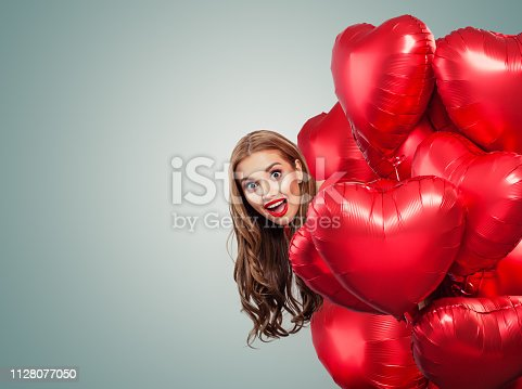 Happy surprised woman withred balloons. Perfect smiling girl with red lips makeup portrait. Surprise, valentines people and Valentine's day banner background with copy space