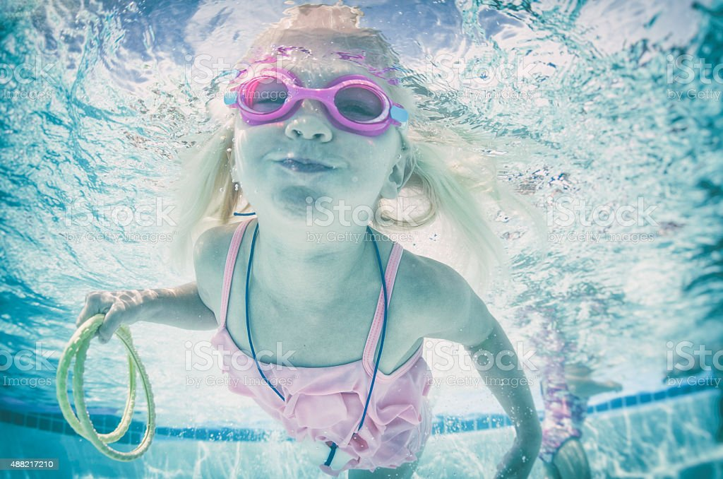 Happy swimming little girl underwater wearing goggles stock photo