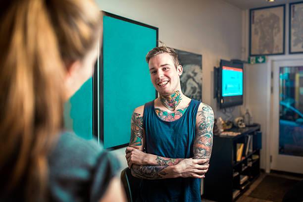 happy tattoo erfahrenen gespräch mit kunden - tattoos frauen arm stock-fotos und bilder