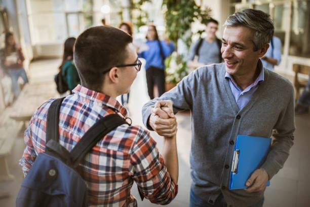 happy teacher and high school student greeting in a hallway. - professore di scuola superiore foto e immagini stock