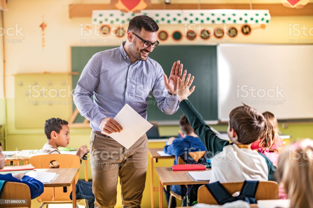 Happy teacher and schoolboy giving each other high-five on a class. Happy male teacher giving high-five to his elementary student on a class in the classroom. Adult Stock Photo