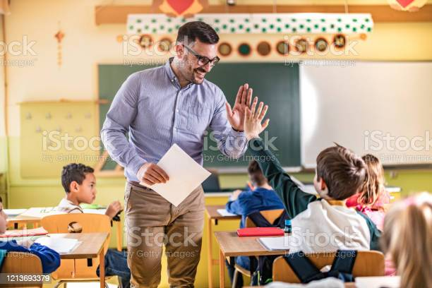 Happy Teacher And Schoolboy Giving Each Other Highfive On A Class Stock Photo - Download Image Now