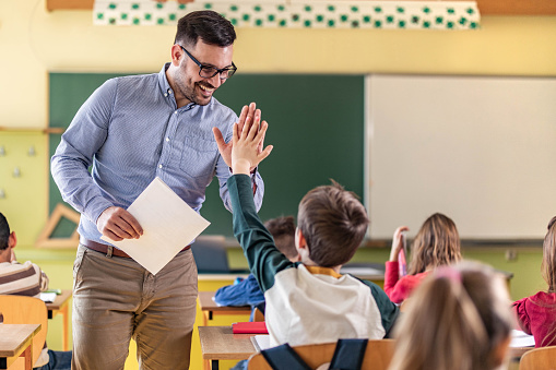 Happy male teacher giving high-five to his elementary student on a class in the classroom.