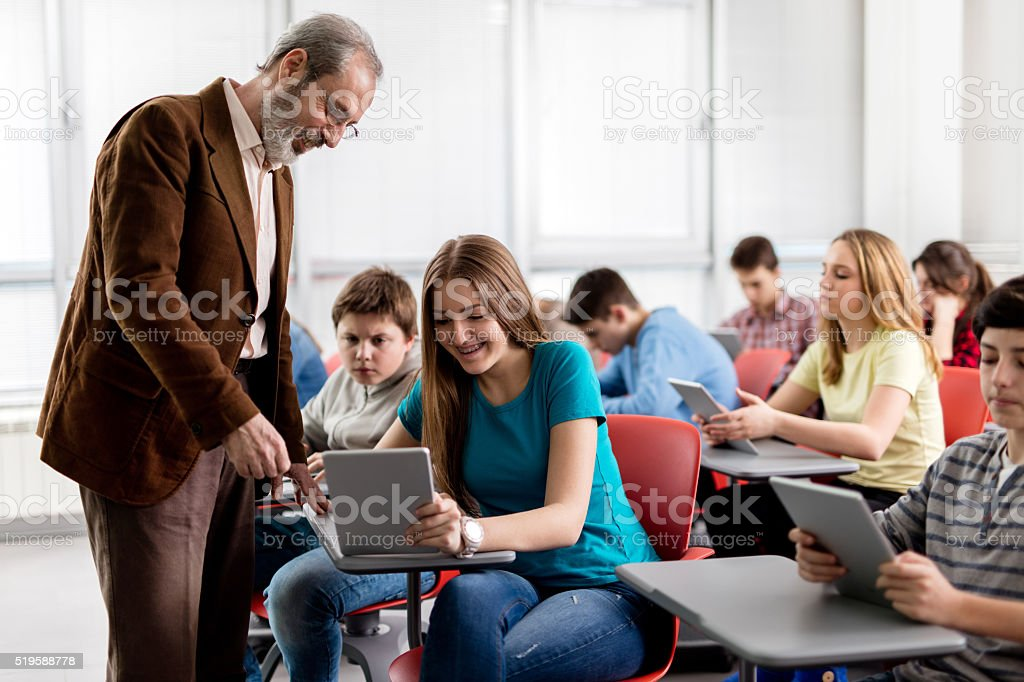 Happy teacher assisting teenage student in a modern classroom. stock photo