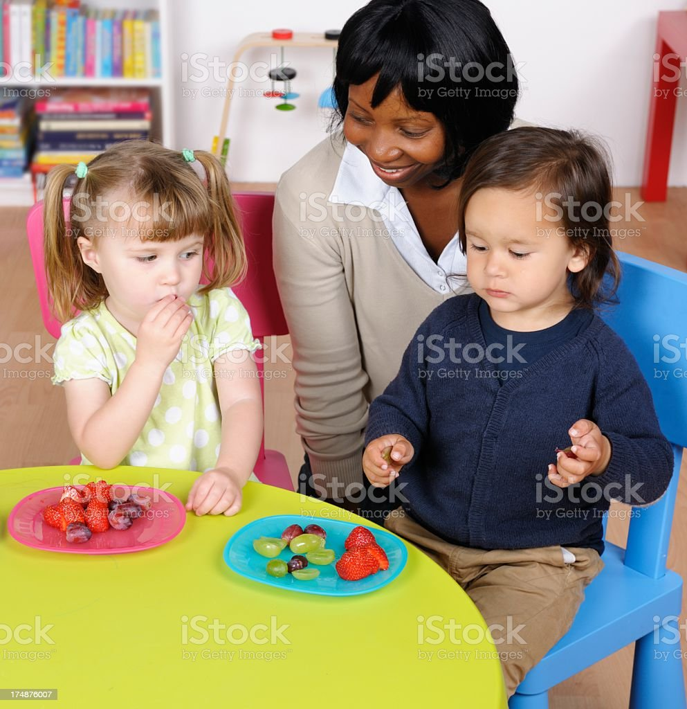 Happy Teacher/ Carer Supervising Little Boy And Girl At Mealtime royalty-free stock photo