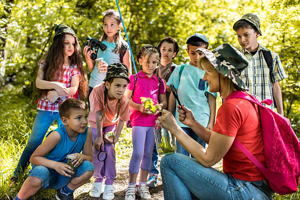 Happy teacher educating group of school children in the park. stock photo