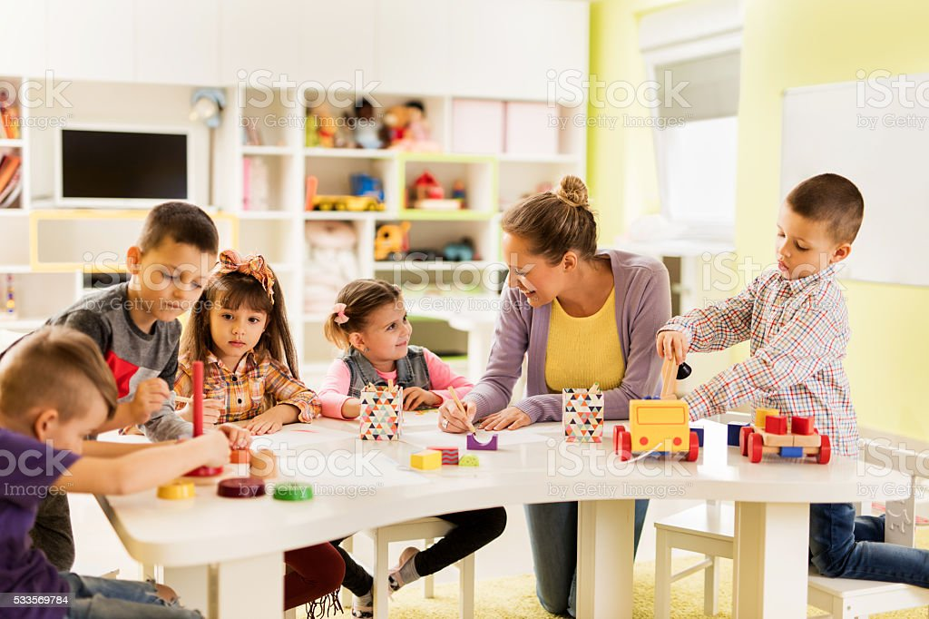 Happy teacher enjoying with group of children at preschool. stock photo