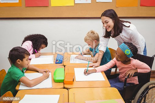 istock Happy teacher helping her students 486095064