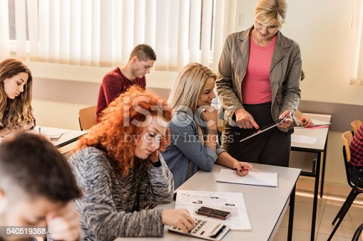 istock Happy teacher showing something on a touchpad to female student. 540519368