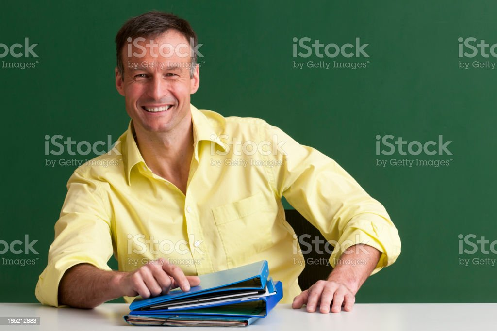 happy teacher sitting at desk royalty-free stock photo