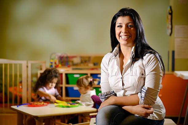 glückliche lehrer mit kindern in bereits im kindergarten essen - erzieherin stock-fotos und bilder