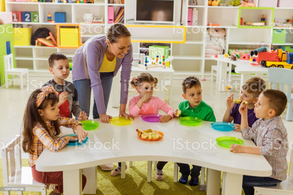 Happy female teacher talking to group of kids while having apples for...