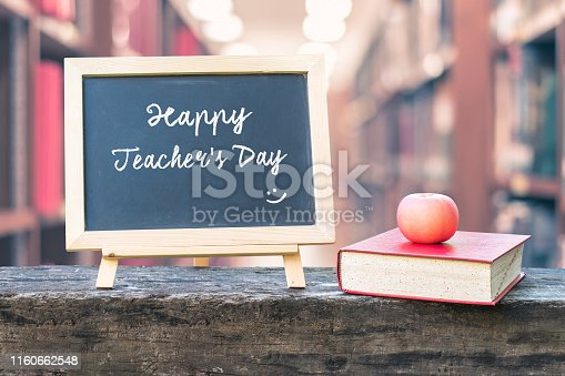 istock Happy teacher's day greeting announcement on black chalkboard on blur school college library background for Education concept 1160662548