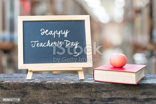 istock Happy teacher's day greeting announcement on black chalkboard on blur school college library background for Education concept 968637118