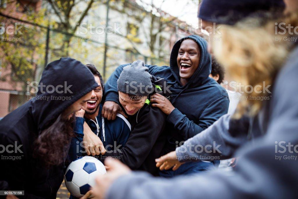 Equipo feliz disfrutando jugando al futbol en la ciudad de - foto de stock