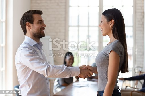 509032417 istock photo Happy team leader shaking hands with smiling female employee. 1185220764