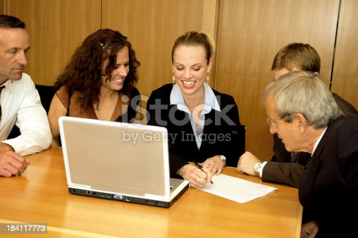 A happy businesswoman writes as her team looks on.