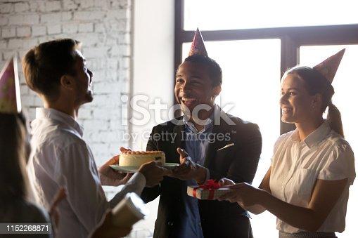 istock Happy teammates congratulating happy birthday to colleague 1152268871