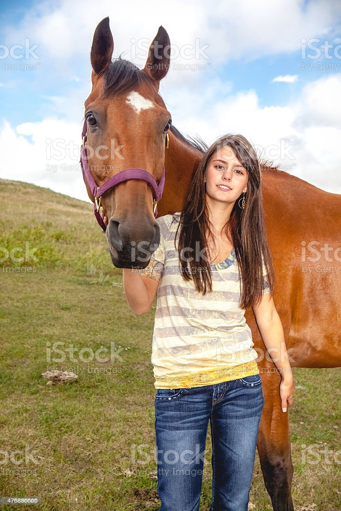 Happy teen girl smiling and standing by her horse stock photo
