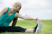 Beautiful Caucasian teenage girl smiles and looks toward the sky as she stretches her muscles before running outside in green grass.