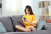 istock Happy teen in yellow using phone at home 1151149224