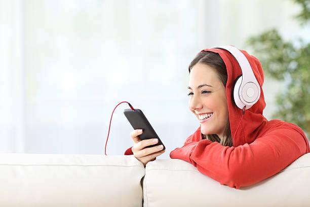 happy teen listening music from phone - geräusche app stock-fotos und bilder