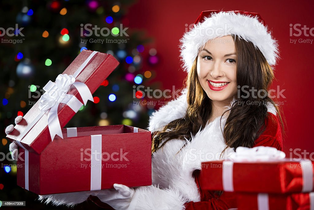 Happy teen opening a gift under the Christmas tree royalty-free stock photo