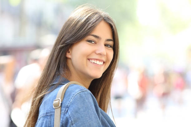 Happy teen smiles looking at camera in the street stock photo