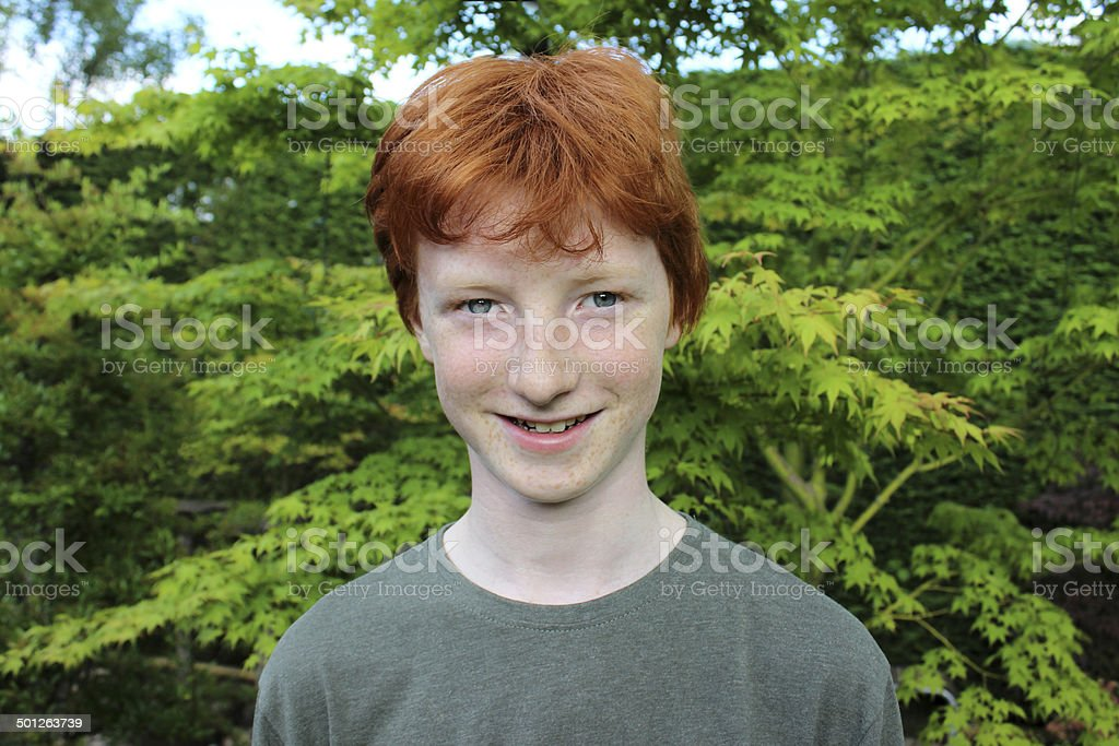 Happy teenage boy in garden, short red hair image, smiling stock photo
