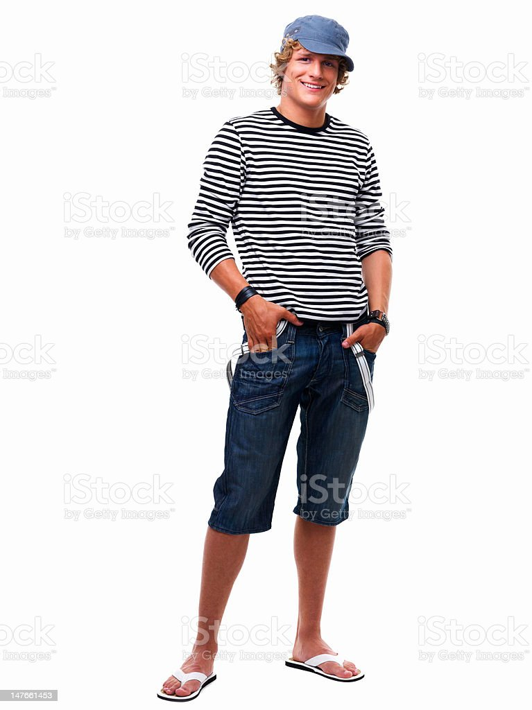 Happy teenage boy standing with hands in pockets stock photo