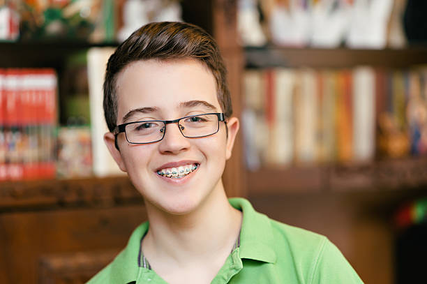 Happy teenage boy with braces and glasses, smiling stock photo