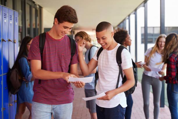 adolescentes felizes compartilhando resultados de exame no corredor da escola - happy test results - fotografias e filmes do acervo