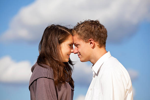 happy teenage couple A happy and smiling teenage couple standing head to head, photographed with blue sky and clouds in the background cute teen couple stock pictures, royalty-free photos & images