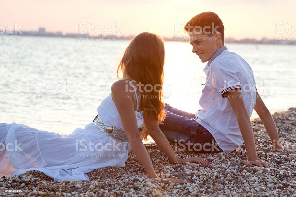 Happy teenage couple sitting together on sea pebble beach royalty-free stock photo