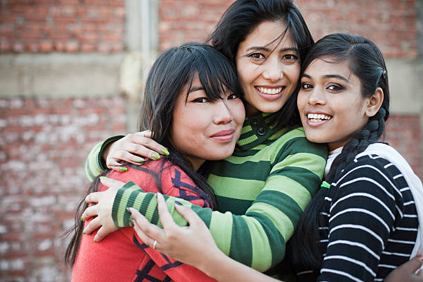 Happy teenage female friends hugging each other with toothy smile. stock photo