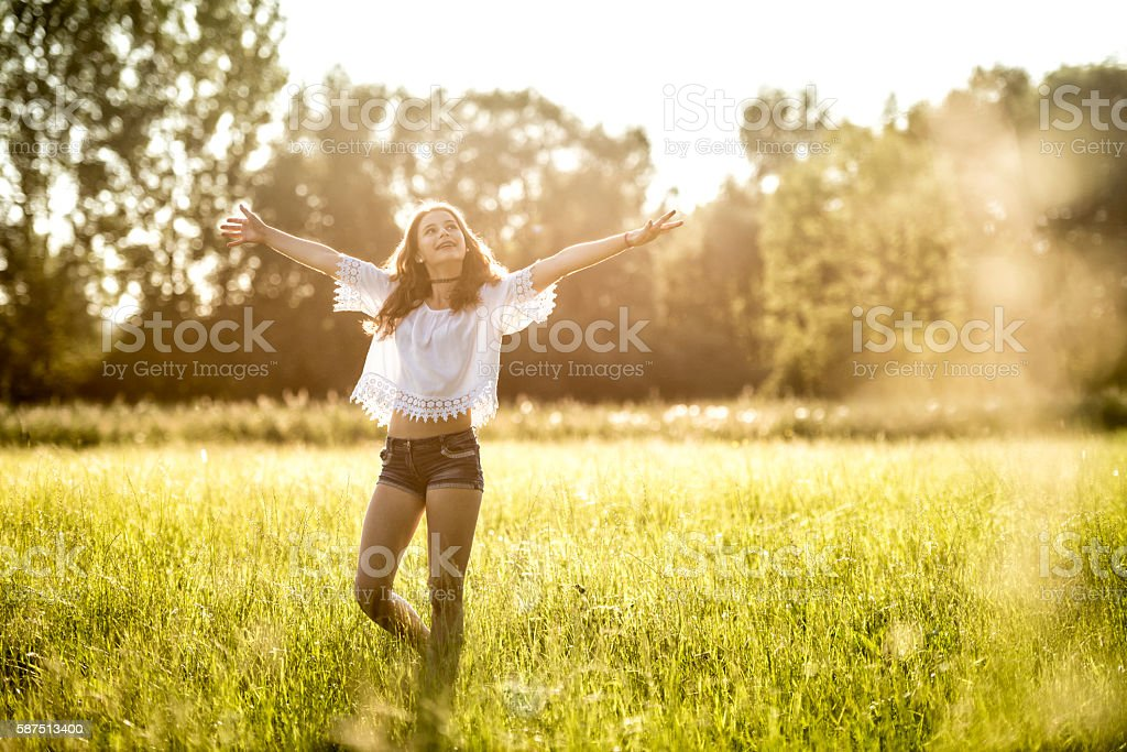 happy teenage girl dancing in meadow stock photo